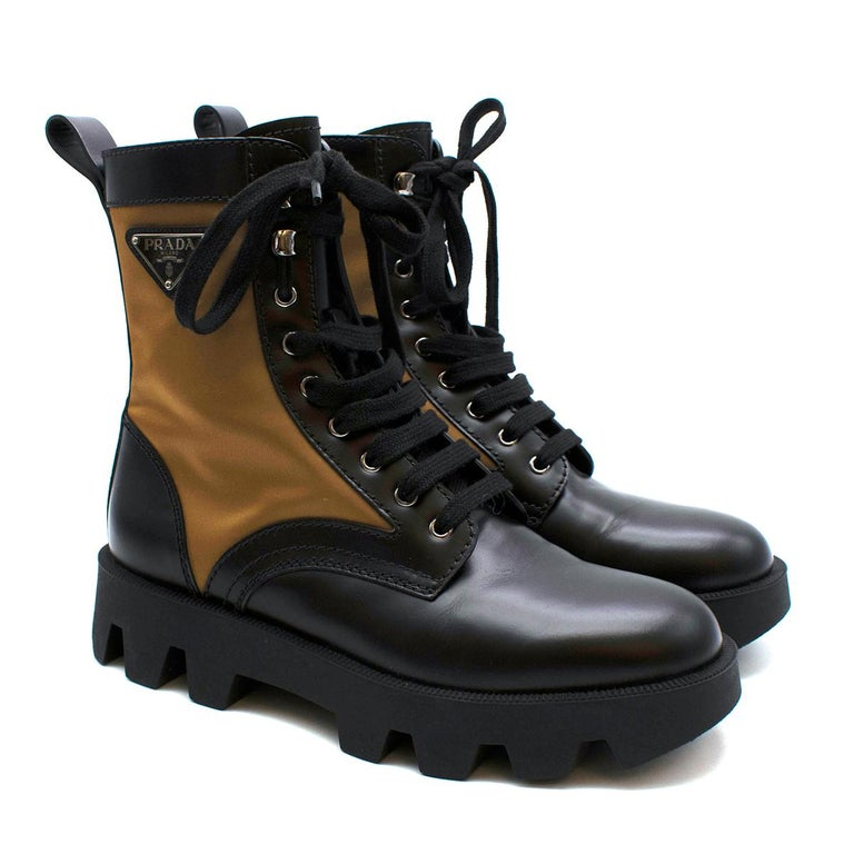 Prada Black & Beige Leather & Nylon Logo Combat Boots  An iconic design characterizes these brushed leather combat boots with large inserts in nylon, a distinctive Prada material. The footwear with metal eyelets and hooks and light lug sole is