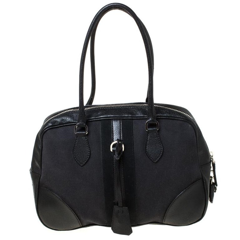 This Bowler bag from Prada is simple in design but highly functional. Crafted from black canvas and leather trims, the bag features two handles, gold-tone hardware and a top zipper leading to a nylon interior for your necessities. The bag will be a