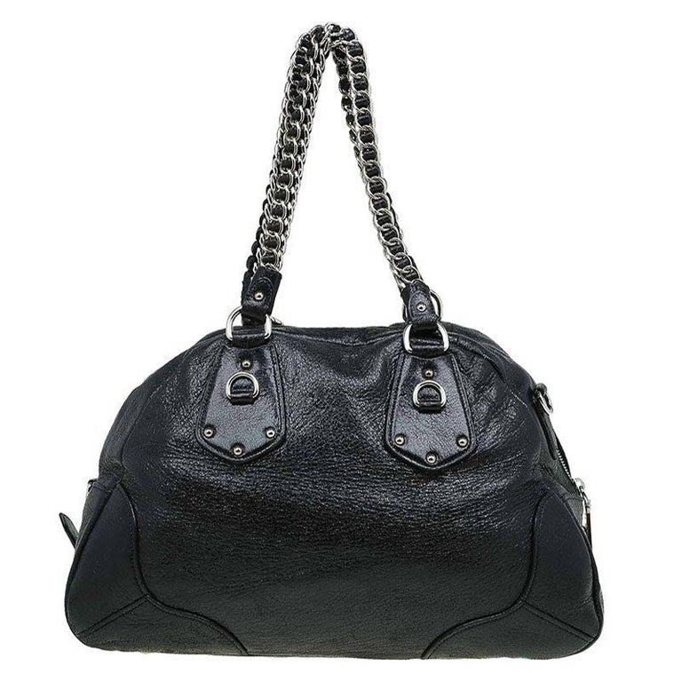 With a distinctive style of its own, this Prada bag is crafted from black Cervo lux leather. It features silver tone hardware with a double leather-metal link chain strap and also, a detachable leather strap and a top zip closure. The triangular