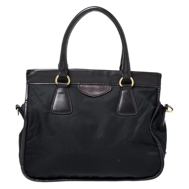 A perfect addition to your wardrobe will be this black tote from Prada. Crafted from nylon and enhanced with leather the tote features dual handles and a shoulder strap. The interior is well-sized and has a zip pocket.  Includes: Original Dustbag,