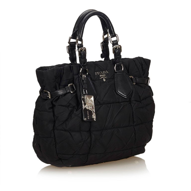 This handbag features a gathered nylon body, rolled leather handles, a top magnetic closure, and an interior zip pocket.   It carries a B+ condition rating.  Dimensions: Length 29 cm Width 40 cm Depth 12 cm Hand Drop 14 cm  Inclusions: No longer