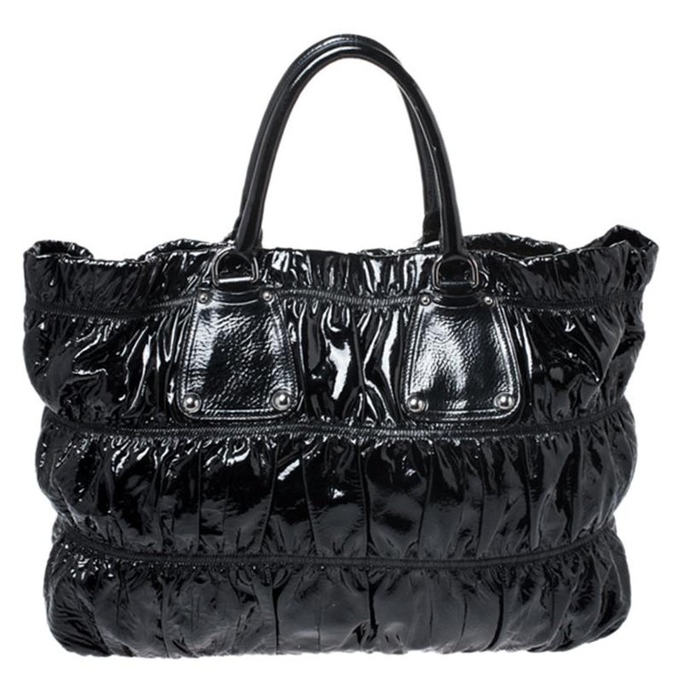 The excellent craftsmanship of this Prada bag ensures a brilliant finish and a rich appeal. This patent leather bag is a fine pick for everyday use. This well-designed bag can hold further than just essentials in its nylon-lined interior.  Includes:
