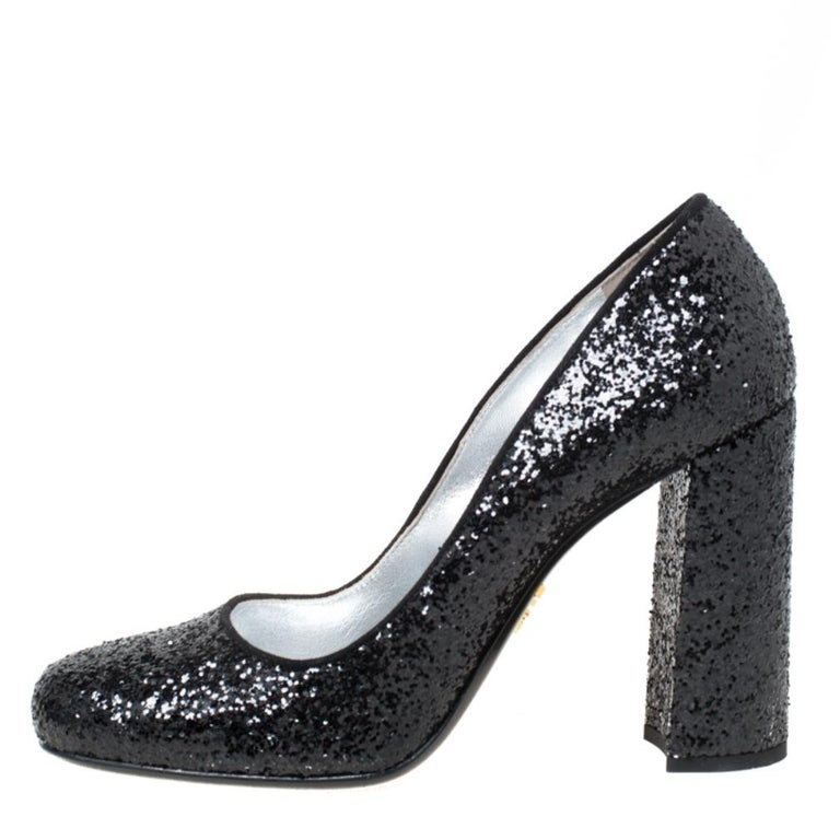 Fashion and comfort come together with these pumps from Prada! Covered in black glitter and shaped into round toes and 10 cm block heels, these pumps will be a winner with all your well-tailored outfits.  Includes: Original Box
