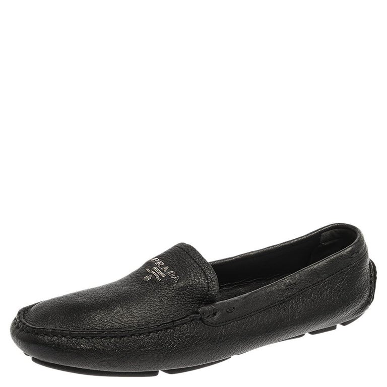 Sleek and stylish, these black loafers by Prada will enhance your outfits by giving them a touch of luxury. Meticulously crafted from grained leather, they carry neat stitches and silver-tone logos on the vamps. The pair is complete with durable