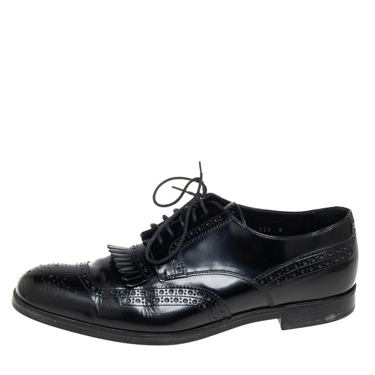 In a grand blend of luxury and practical style comes this pair of derby shoes from Prada. The designer shoes are covered in black leather and designed with laces and fringe detailing on the vamps. They are elevated on low heels.