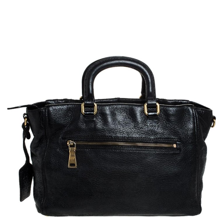 Add some magic to your everyday attire with this super stylish and classy handbag by Prada. Crafted from quality leather, it comes in a stunning shade of black. It comes with dual handles, a detachable strap, an exterior zip pocket with a push-lock