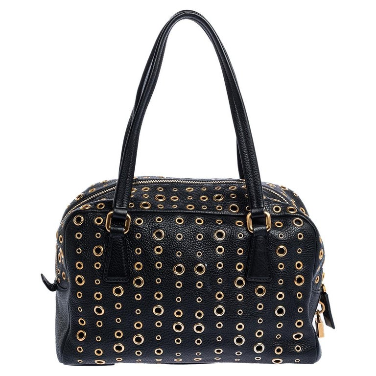 When you carry this Prada creation, be ready to catch admiring glances as this bag is stylish and handy. The bag has been crafted from leather in a lovely black shade and designed with gold-tone grommet embellishments all over as well as two top