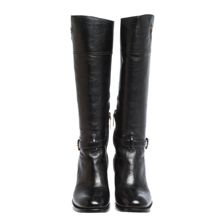 Prada elevates your style quotient by giving you just the right amount of luxury with this gorgeous pair of black boots. They are cut to a knee-length and feature round toes, buckle and logo detailing in gold-tone and low heels.  Includes: Info