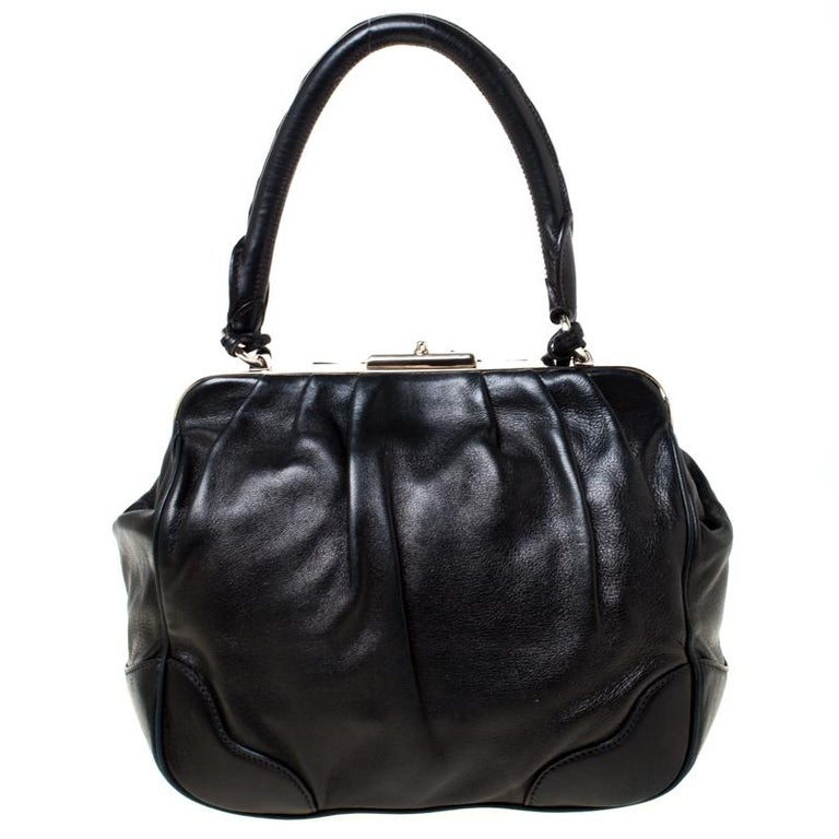 This well-designed satchel from Prada is crafted from black leather with silver-tone metal framed top. The exterior of the bag is adorned with subtle pleats, tassels and a leather tag. It has a nylon-lined interior featuring a zip pocket. Held by a