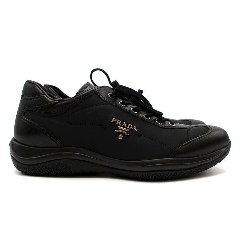 Prada Black Leather Nylon Low-Top Sneakers  - Calf leather with nylon technical fabric upper - Prada metal logo on the side - Prada signature logo tag on tongue - Low-top style  - Lace-up closure  - Rubber outsole with Prada signature heat embossed