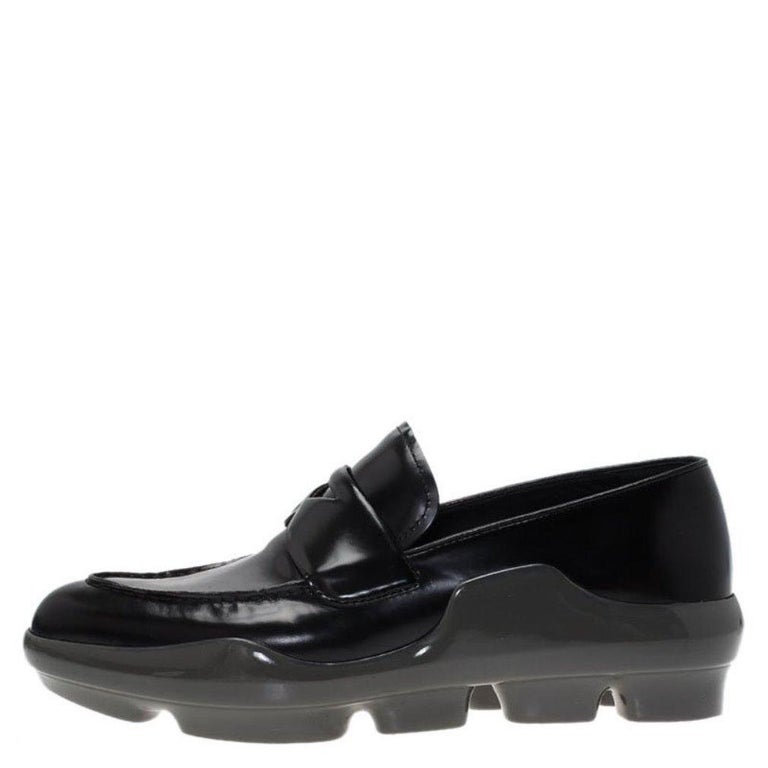 These black patent leather shoes from Prada have an extra thick sole forming the platform. The apron toe and boat opening adds to the comfort of wearing the shoes. The penny keeper strap at the vamp looks stylish.  Includes: Original Dustbag