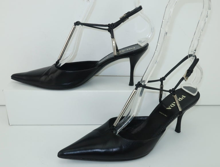 Prada creates a classic wardrobe staple in a black leather t-strap shoe and adds a modernist touch with silver metal logo accents.  The slingback design has an adjustable buckle and the 3