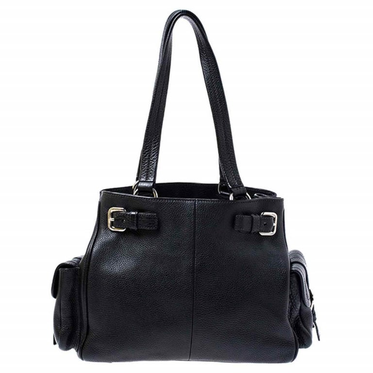 Look classy and sophisticated when you carry this Prada bag. Get yourself this stylish leather bag for a modern look. It is lined with nylon to store your essentials which adds to its functionality. The bag flaunts dual handles, side pockets and the