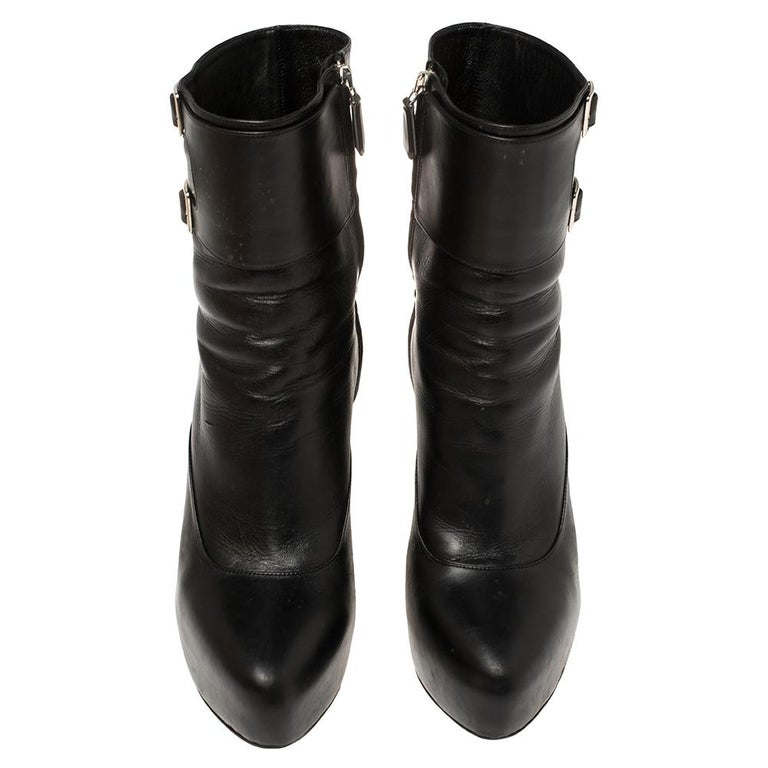 Prada elevates your style quotient giving you just the right amount of attention with this amazing pair of black ankle boots. These fabulous leather boots make for comfortable wear. They are styled with almond toes, dual buckle straps, side zippers,