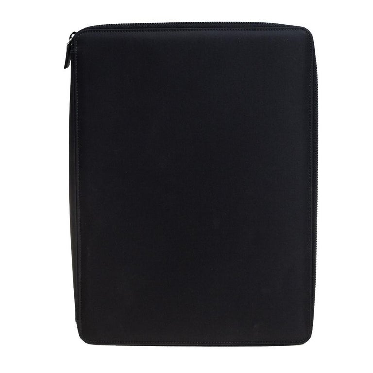 This Prada document holder made from black nylon is perfect for carrying your work documents in style. It has a leather-lined interior equipped with slots for cards, pens, papers and is secured with a zipper.