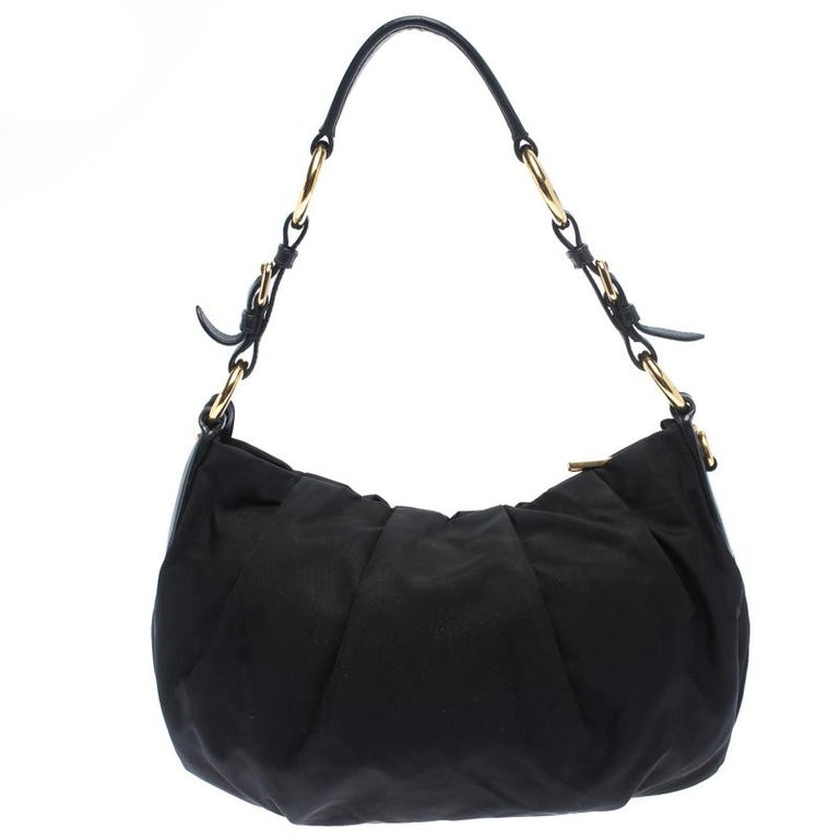 Make stunning addition to your accessory collection with this rich and fabulous Prada bag. Crafted from nylon with interiors lined in fabric, this bag is skillfully crafted. The bag features a single handle and gold-tone hardware.  Includes: The