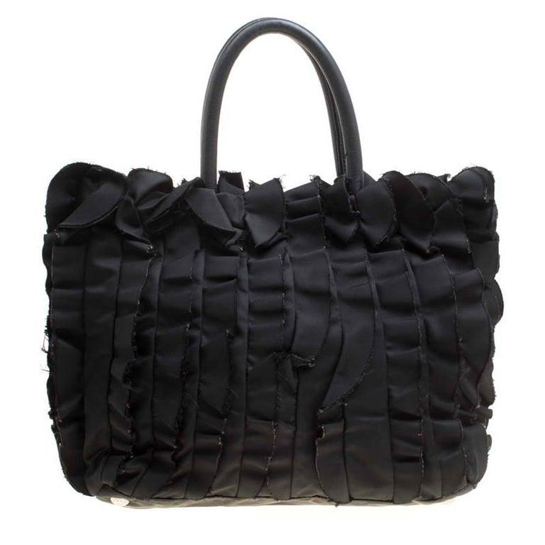 A single look at this pretty Prada creation will steal your heart away. Rendered in black nylon, the tote is designed with utterly feminine aesthetics featuring ruffled patterns all over. The snap button closure on the top leads you to a nylon-lined