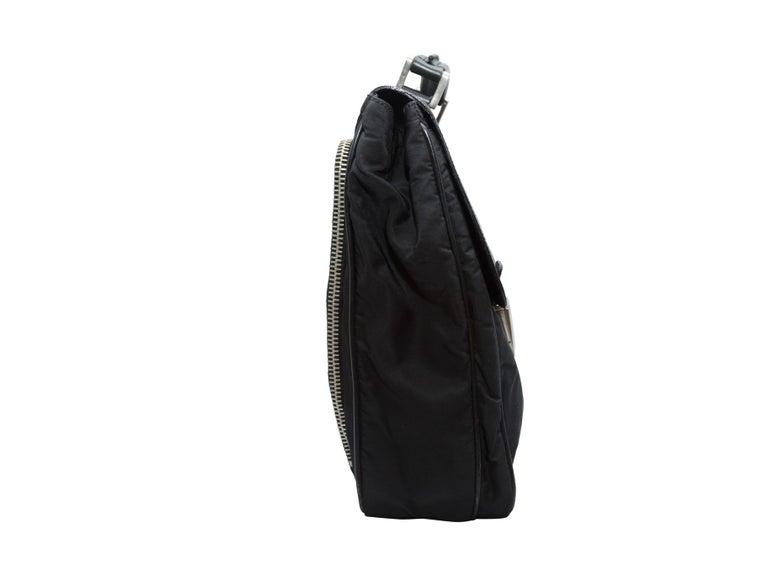 Product details: Vintage black nylon and Saffiano leather briefcase by Prada. Zip pocket at back. Buckle closures at front flap. 15