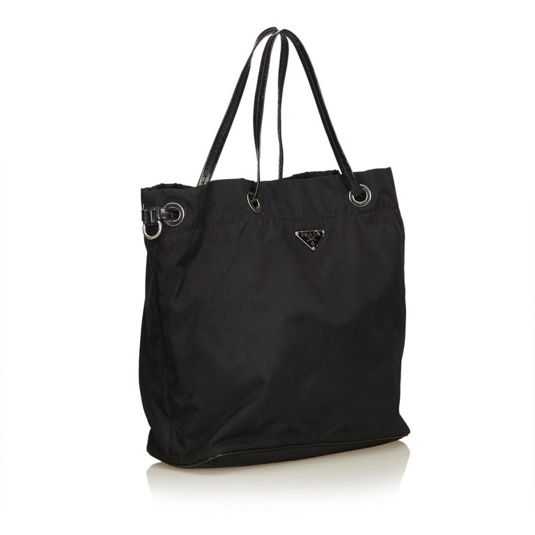This tote bag features a nylon body, flat leather straps, open top, and an interior zip pocket. It carries as B+ condition rating.  Inclusions:  This item does not come with inclusions.  Dimensions: Length: 29.50 cm Width: 39.00 cm Depth: 13.00