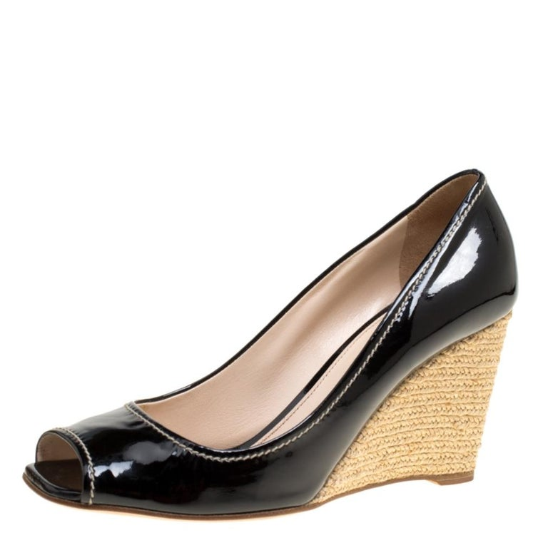 Feminine and classy, these pumps by Prada are just irresistible. They carry a glossy black exterior made from patent leather and styled with peep toes. Leather insoles and espadrille wedges wonderfully complete the pair.  Includes: Original Dustbag