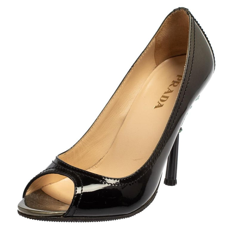 These fabulous pumps from Prada will lend a luxurious appeal to your looks. They are crafted from patent leather in black and feature peep-toes and neat stitching throughout. They come equipped with comfortable leather-lined insoles and stand tall