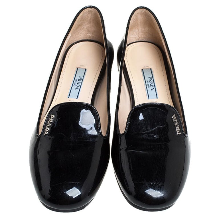 Keep it casual and chic in these black slip-on loafers from Prada. They come crafted from patent leather and feature round toes and brand logo detailing on the vamps. They are complete with comfortable leather-lined insoles and durable rubber