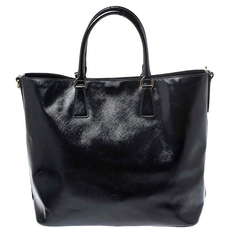 When you carry this Prada creation, be ready to catch admiring glances as this tote is stylish and handy. The bag has been crafted from black patent leather. It is equipped with dual top handles and it has a very spacious nylon-lined interior that