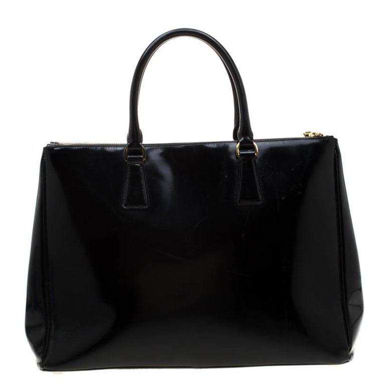 This elegant Spazzolato tote from Prada is crafted from patent leather and is perfect for daily use. The bag features double handles, a leather covered gold key ring, protective metal feet, and gold-tone hardware. It has a nylon lined interior that