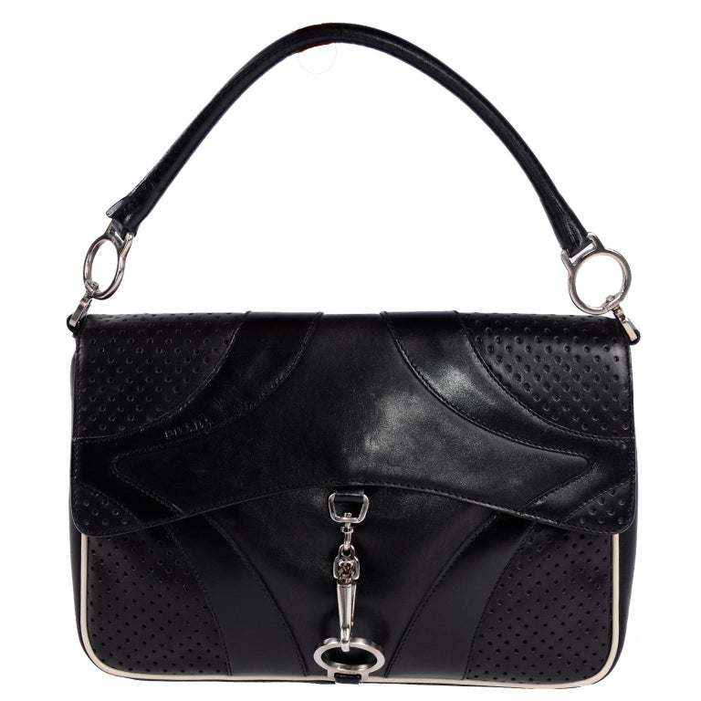 This is a great on trend authentic Prada Black Leather handbag with silver hardware, perforations and top-stitch quilting.  This vintage bag has an Inside zip pocket and white trim leather