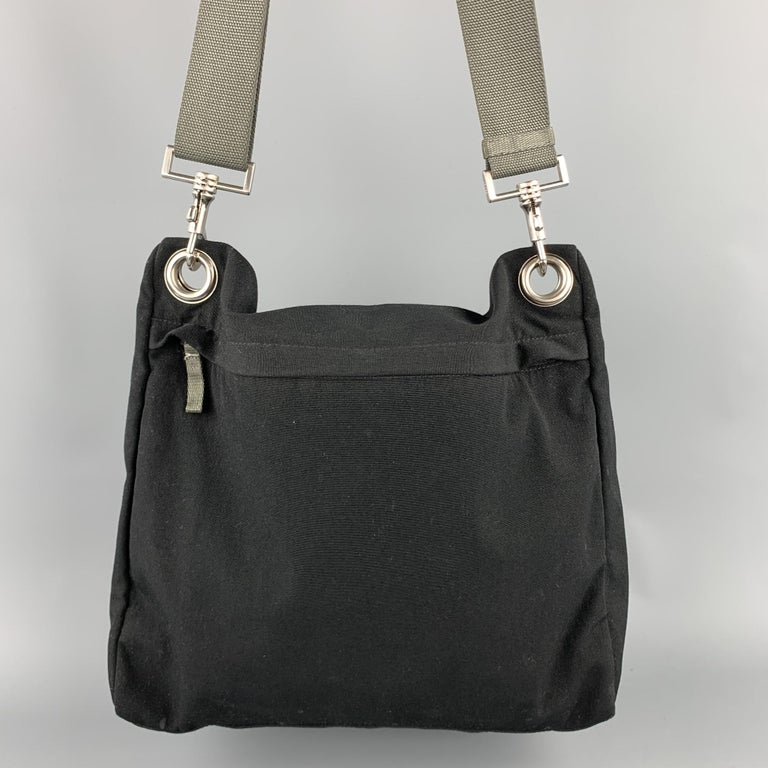 PRADA messenger handbag comes in a black canvas with a gray removable shoulder strap featuring a inner zipper pocket and a zip up closure. Made in Italy.  Very Good Pre-Owned Condition.  Measurements:  Length: 13 in.  Width: 5 in.  Height: 12 in.