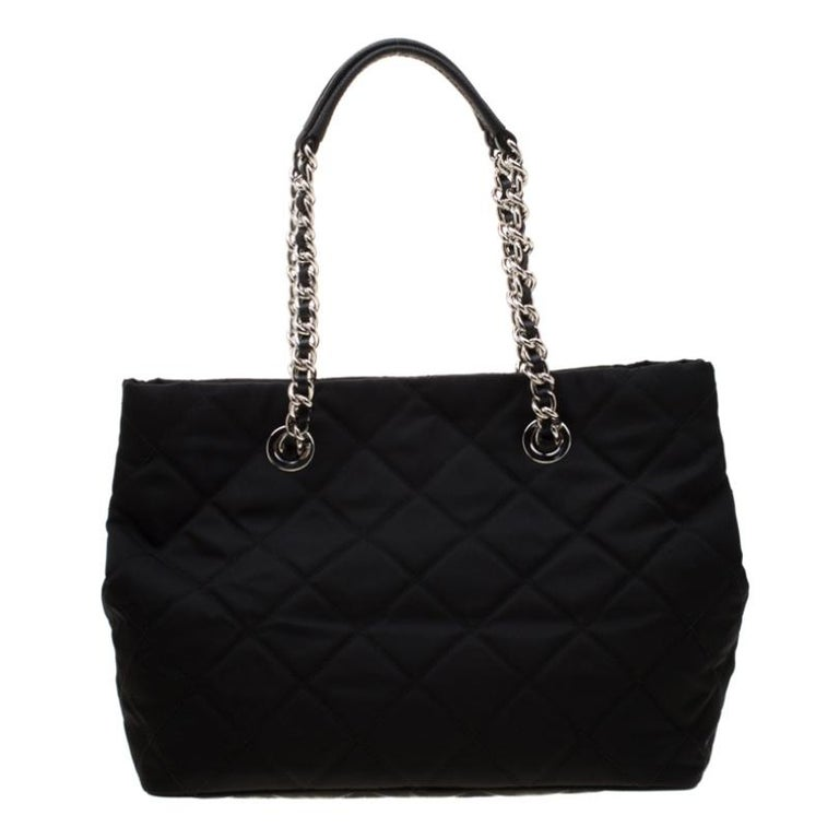 Impeccably crafted this Prada bag is perfect for the stylish woman in you. The black nylon bag comes with interwoven chain handles, quilted exterior and an open top. The interior is spacious and features a zipped compartment that will safely hold