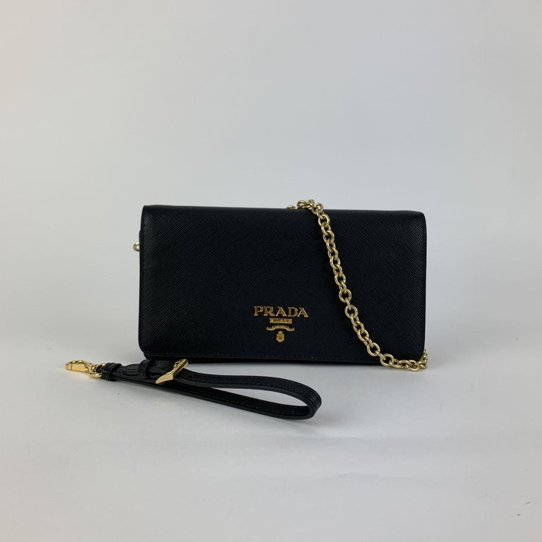 Prada black Saffiano leather flap continental wallet on chain/WOC, mod. 1DH029. Gold metal hardware. PRADA Metal lettering logo. Double magnetic button closure. 2 credit card slots. 1 coin compartment with zipper, 2 bill compartment and 3 open