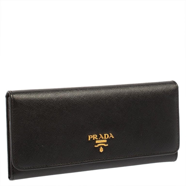 Basic essentials can be carried effortlessly in this black Prada continental wallet. Crafted from Saffiano leather, the flap style wallet features the brand detail at the front and inside. It has multiple card slots, open compartments, and a zip