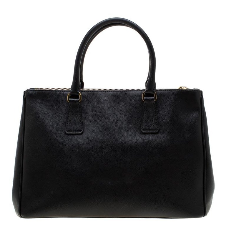 Feminine in shape and grand on design, this Double Zip tote by Prada will be a loved addition to your closet. It has been crafted from Saffiano leather and styled minimally with gold-tone hardware. It comes with two top handles, two zip compartments