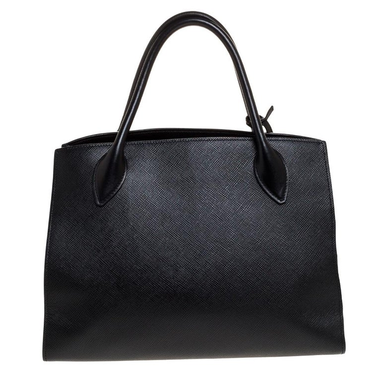 This stylish tote bag by Prada has been crafted to assist you with ease and style on all days. It is crafted from black Saffiano leather. The sleek tote features two handles, a detachable shoulder strap and a spacious interior.  Includes:Original