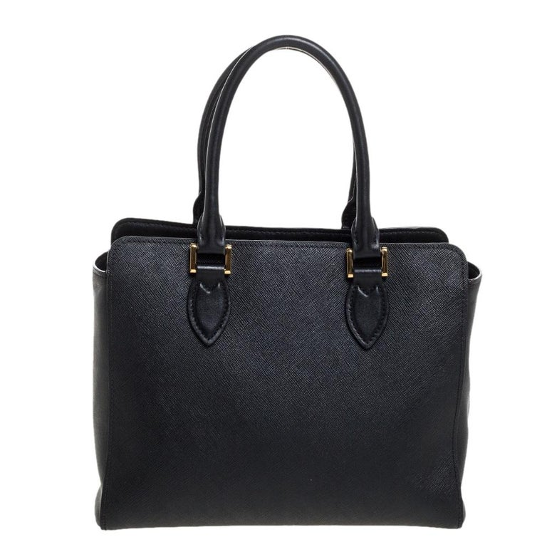 Loved for its classic appeal and functional design, Galleria is one of the most iconic and popular bags from the house of Prada. This beauty in black is crafted from Saffiano Lux leather and is equipped with two top handles, the brand logo at the