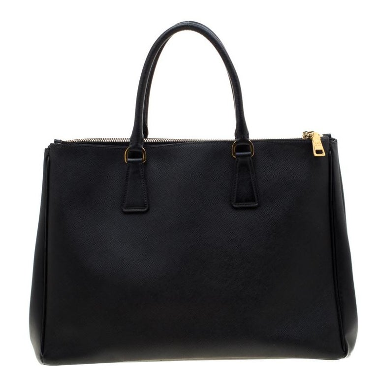 Feminine in shape and grand on design, this Double Zip tote by Prada will be a loved addition to your closet. It has been crafted from saffiano lux leather and styled minimally with gold-tone hardware. It comes with a nylon interior that has two zip