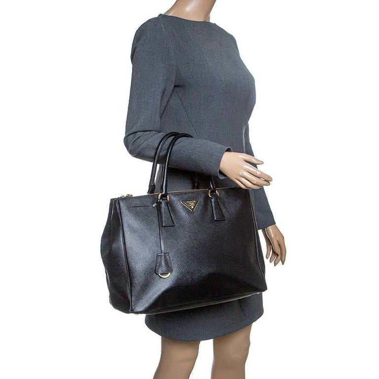 Beautifully crafted from Saffiano Lux leather, this Prada tote is a creation you can't miss. It has a classy black exterior along with two zippers and a spacious nylon interior that will hold your necessities. The bag is held by two handles and is