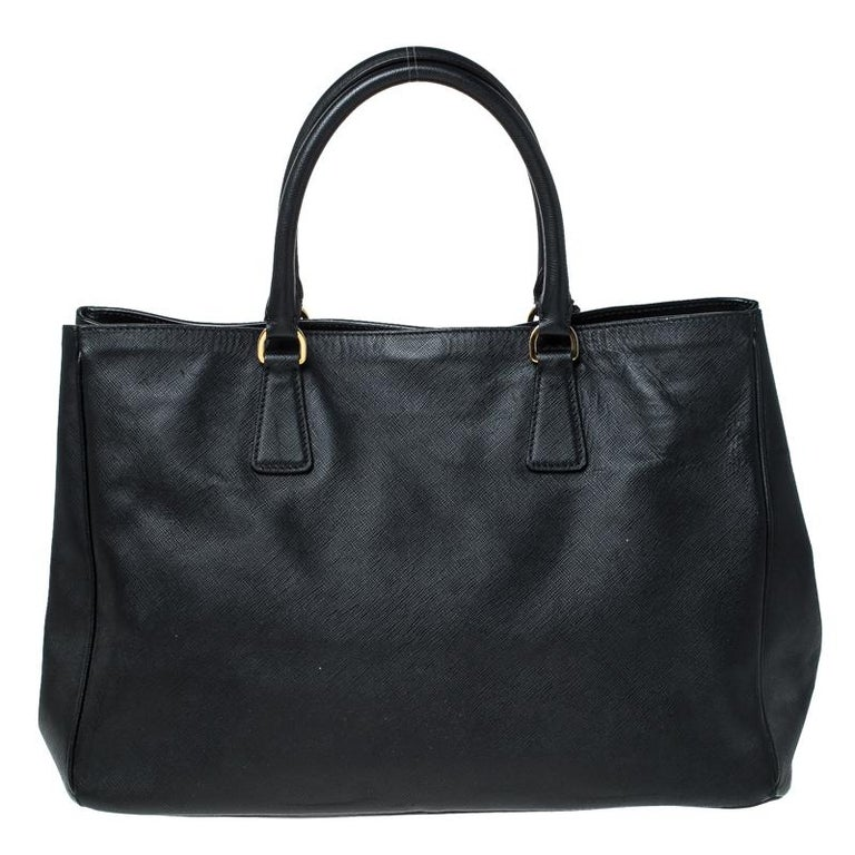 High in appeal and style, this tote is a Prada creation. It has been crafted from leather and shaped to exude class and luxury. The bag comes with two handles and a spacious nylon interior for your ease. Protective metal feet and the brand logo on