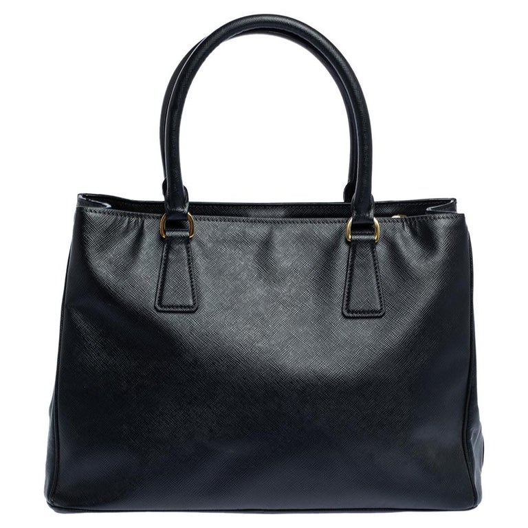 This elegant tote from Prada is crafted from leather and is perfect for daily use. The bag features double handles, protective metal feet, and a removable shoulder strap. The bag opens to a nylon-lined interior. The black tote is spacious enough to