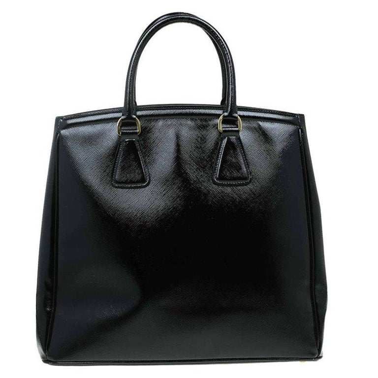 This Prada tote is luxurious and crafted from the finest Saffiano lux leather in black. This bag has a roomy interior with a pocket and top zipped closure, perfect for everyday essentials. Featuring gold tone hardware, the iconic triangular logo and