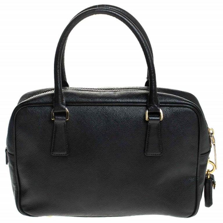 This stunning satchel is high on appeal and style. Dazzling in a classy black shade, the bag is crafted from Saffiano Lux leather and features two rolled handles. The zip closure leads way to a nylon interior with enough space for your essentials