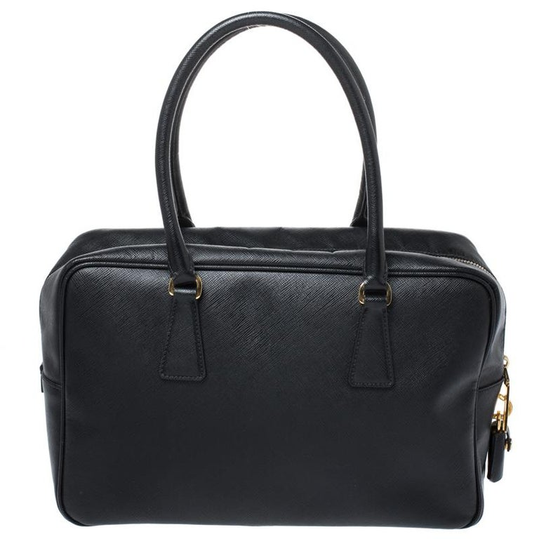 Masterfully created, this Prada satchel is a style icon. Designed in a Saffiano Lux leather body, it exudes style and class in equal measures. This delightful black piece is held by two top handles and equipped with a spacious nylon