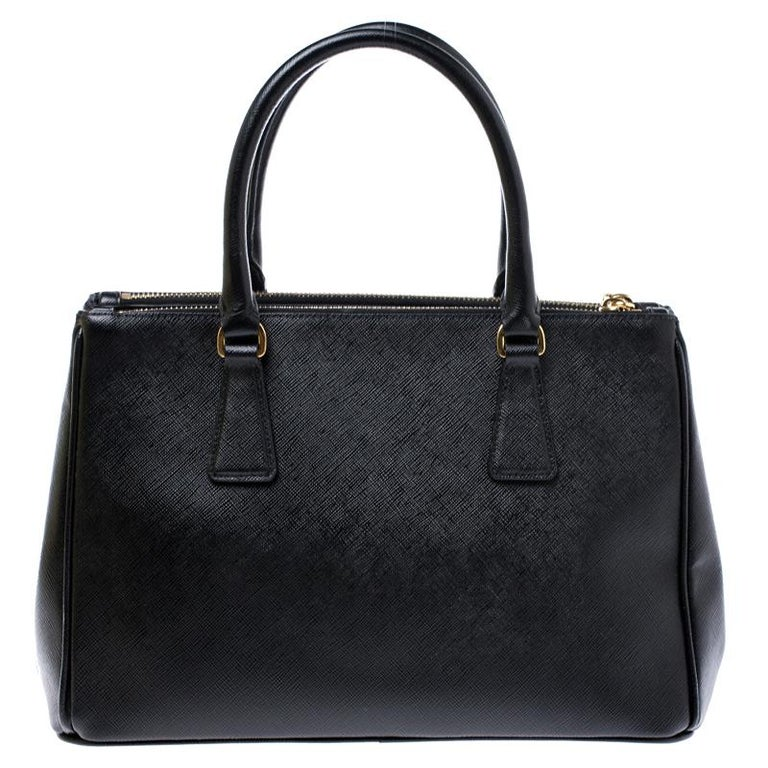 Feminine in shape and grand on design, this Double Zip tote by Prada will be a loved addition to your closet. It has been crafted from leather and styled minimally with gold-tone hardware. It comes with two top handles, two zip compartments and a
