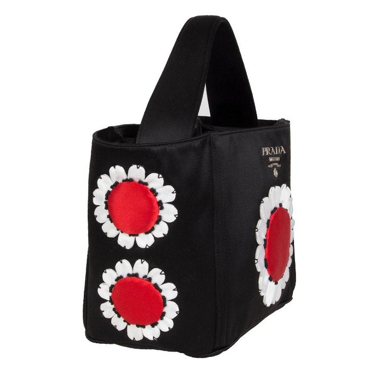 Prada 'Raso Flower' basket handbag in black, red and white satin. Divided into three compartements. The middle one closses with a snap button. One side compartment has one zipper and one open pocket and the other side has one zipper pocket. Has been
