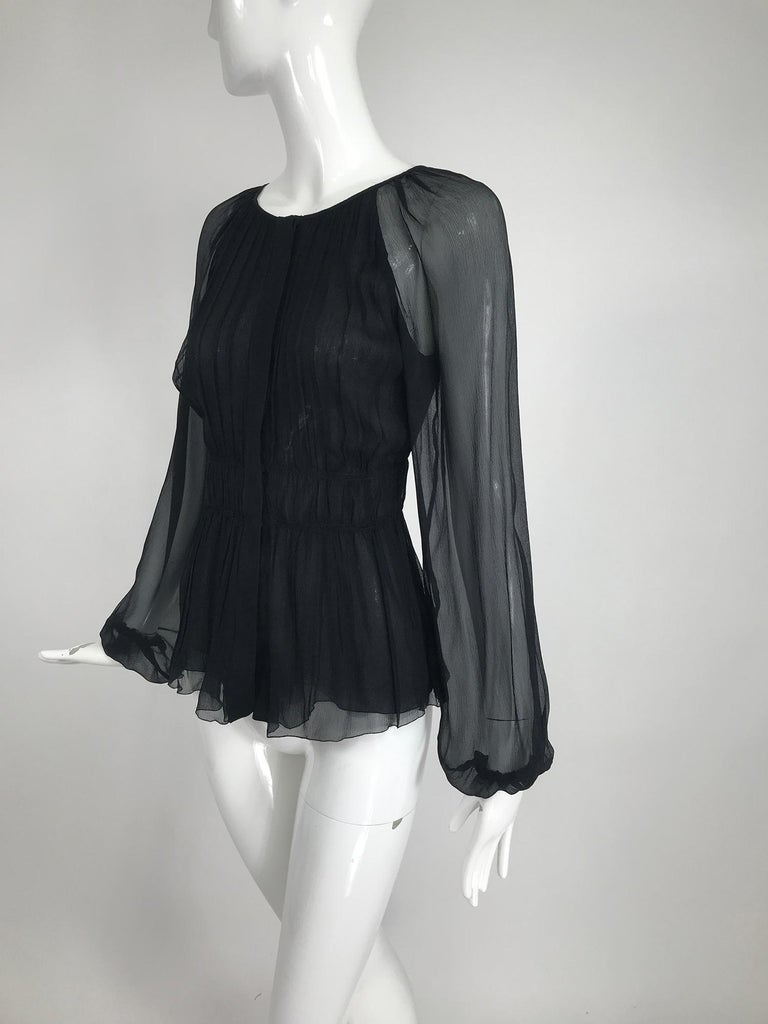Prada sheer black silk chiffon jewel neck, blouse with a pleated gathered fitted torso and double narrow band waist. Long raglan sleeves are full and have cased elastic cuffs. The blouse closes at the front with buttons and hidden snaps. Blouse is
