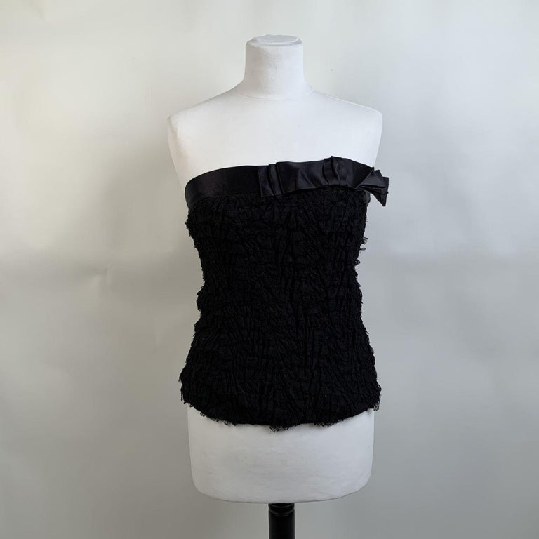 Prada bustier top in black color, with allover lace applications. Bow detailing on the neckline. Side button and hook and eye closures. Composition: 100% Silk. Application: 47% Nylon, 53% Viscose. Trimmings: 100% Silk. Size 40 IT (it should