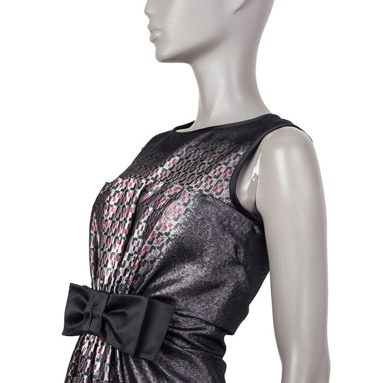 Prada sheath dress in black, silver, and red silk (73%) and polyester(27%). With round neck, pleated front held by a black satin bow on the waist, black satin trims, and horizontal pleats on the back. Closes with concealed metal zipper on the back.