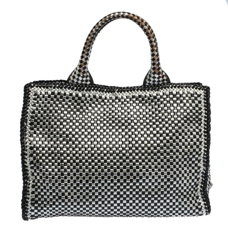 This eye-catching tote from Prada has a timeless charm. The bag is woven from leather in black and silver. It has dual round handles, a detachable shoulder strap and protective metal feet at the bottom. Ideal for everyday use, the bag has enough