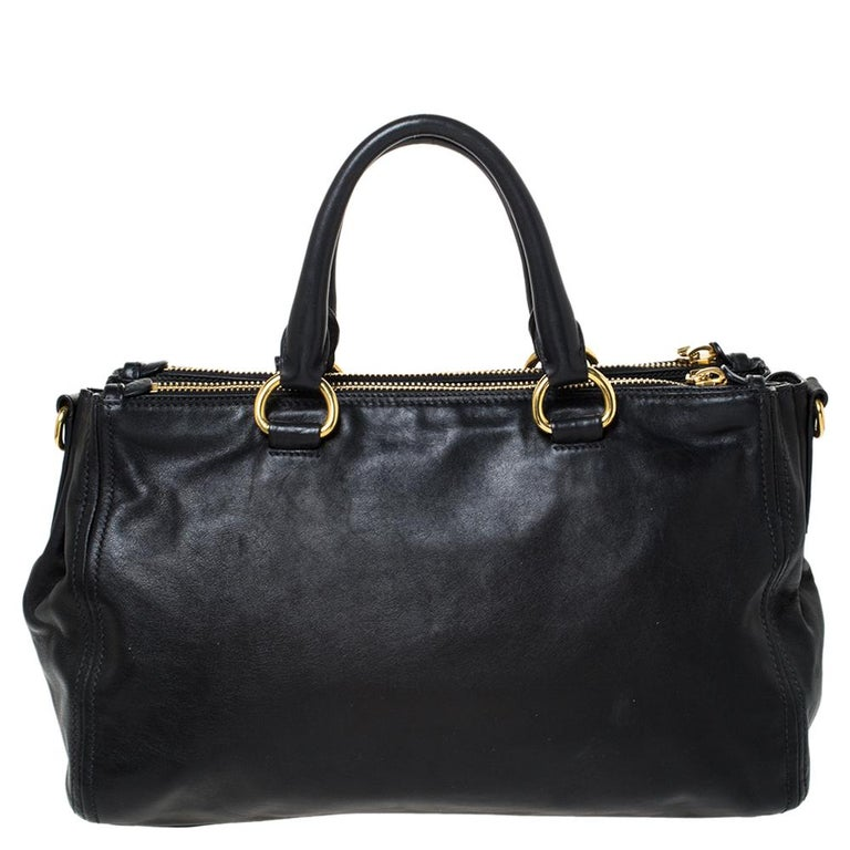 Feminine in shape and grand on design, this Double Zip tote by Prada will be a loved addition to your closet. It has been crafted from soft calf leather and styled minimally with gold-tone hardware. It comes with two top handles, two zip